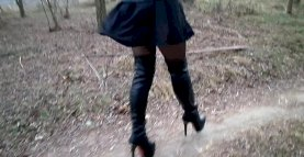 High boots, short dress, legs in pantyhose and strong wind